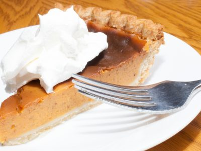Sweet potato pie on a white plate that has whipped creme
